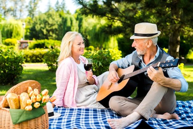 Oude man gitaar spelen voor zijn vrouw