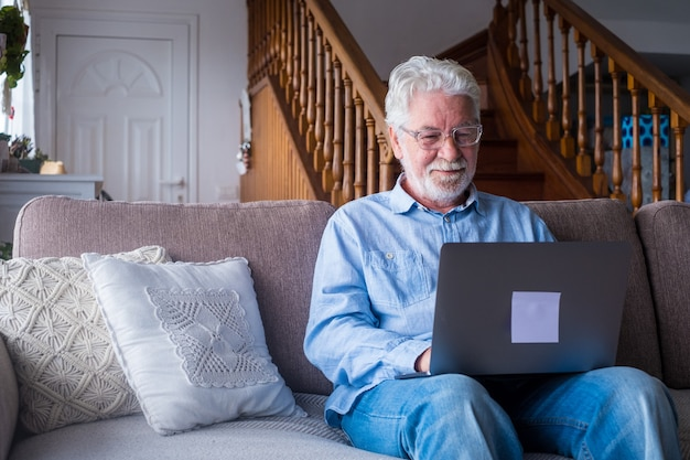 Oude man glimlachend zittend op de bank in de woonkamer met behulp van laptop, genietend van werken met de computer, tevreden voelen met het verzenden van berichten, vrienden bellen, surfen op het web online concept