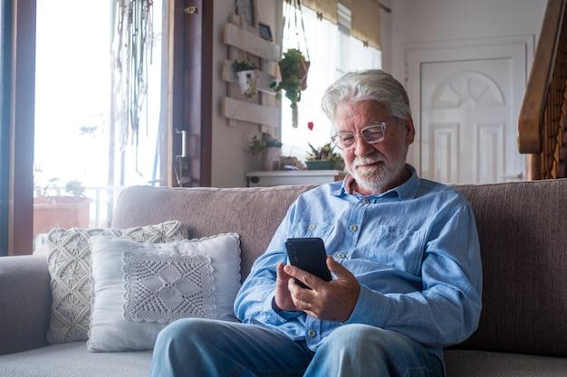 Oude man glimlachend zittend op de bank in de woonkamer met telefoon, genietend van het gebruik van smartphone, tevreden voelen met het verzenden van berichten, vrienden bellen, surfen op web online concept