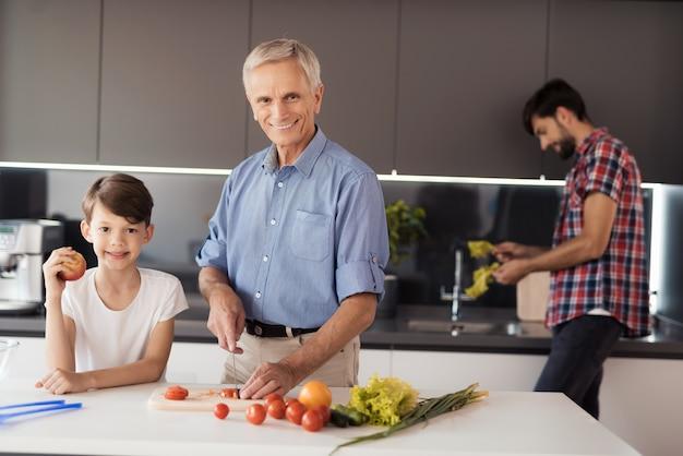 Oude man in blauw shirt poseren in keuken met zijn kleinzoon.