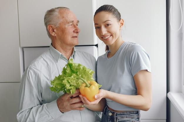 Oude man in een keuken met jonge kleindochter