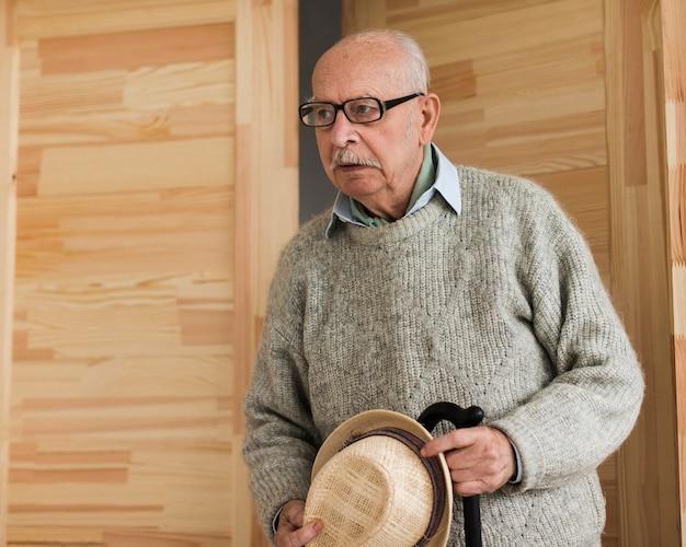 Oude man in een verpleeghuis met stok en hoed