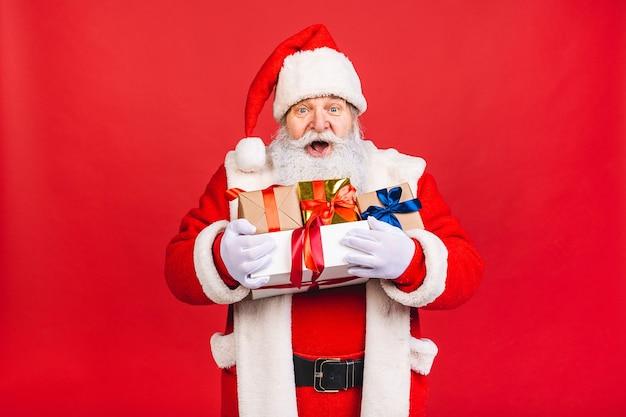 Oude man in santa claus kostuum met een stapel cadeautjes geïsoleerd op rode achtergrond
