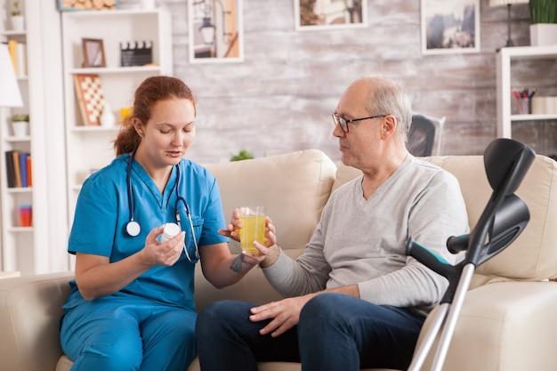 Oude man in verpleeghuis geholpen door vrouwelijke arts om zijn medicijn in te nemen.