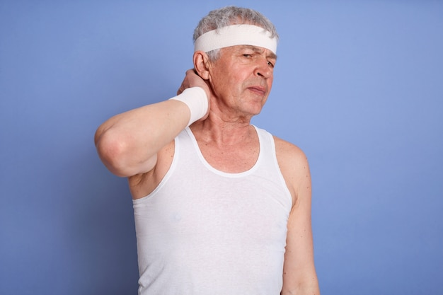 Oude man in wit t-shirt met nek pijn geïsoleerd, raakt haar nek, heeft letsel tijdens sporttraining, sportieve man met haarband.