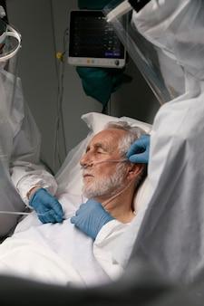 Oude man in ziekenhuisbed die een beademingsapparaat nodig heeft