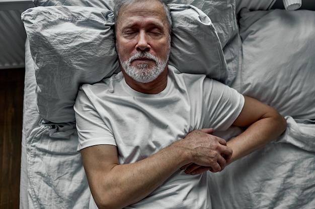 Oude man is gestrest door ziek te worden op bed, hand in hand op de borst, hij kreeg de diagnose hoge bloeddruk en kanker.
