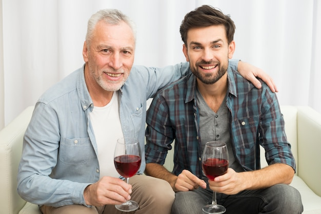 Oude man knuffelen jonge lachende man met glazen wijn op sofa