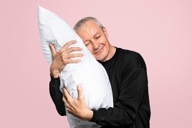 Oude man knuffelt een kussen voor een goede nachtrust