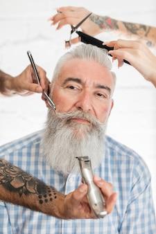 Oude man krijgt haar en baard verzorgen