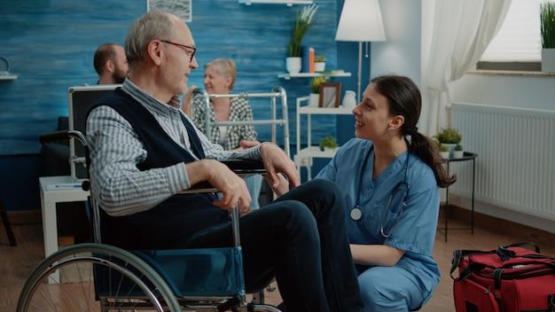 Oude man krijgt medisch bezoek van vrouwelijke verpleegster