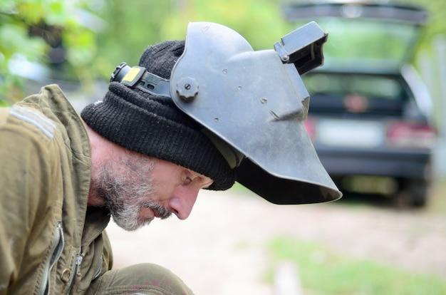 Oude man lasser in bruin uniform bereidt metalen deur oppervlak voor het lassen