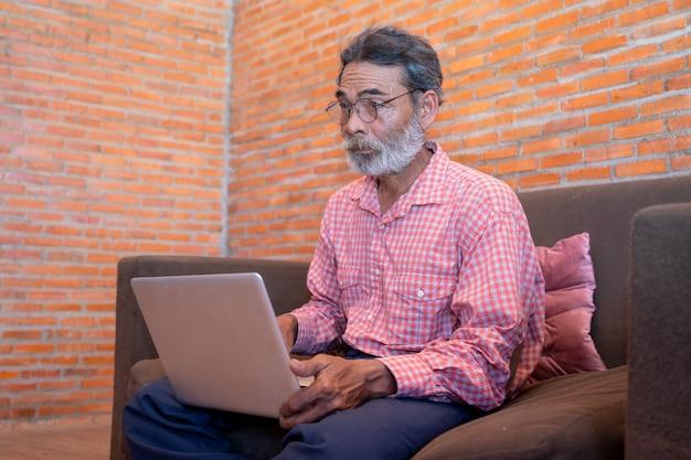 Oude man leren om een laptop thuis te gebruiken, senior man computerwerk thuis gebruiken