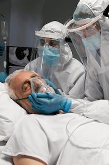 Oude man ligt ziek in een ziekenhuisbed naast artsen