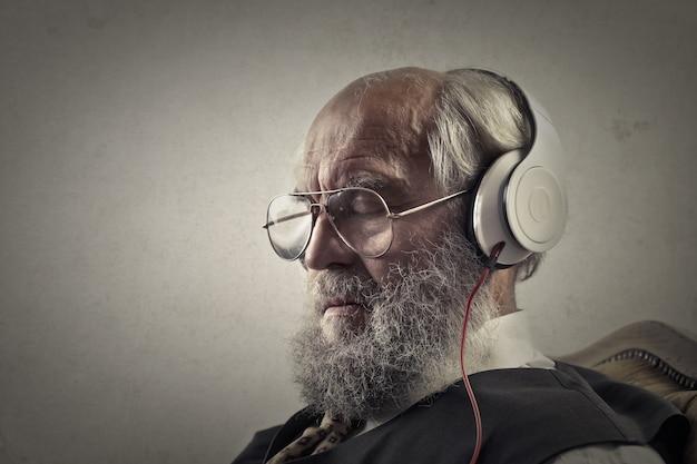 Oude man luisteren naar muziek