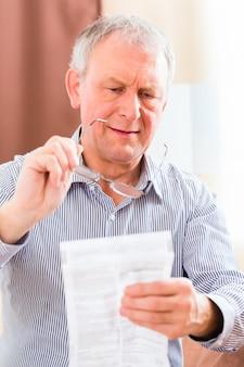Oude man medicijn bijsluiter thuis lezen met een bril