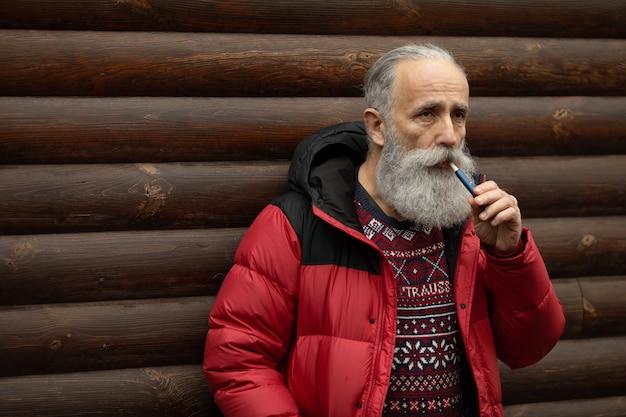 Oude man met baard en snorren in een roze t-shirt roken.