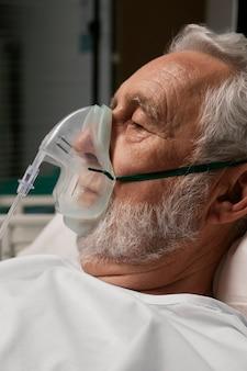 Oude man met beademingsapparaat in een ziekenhuisbed