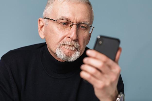 Oude man met behulp van telefoon portret