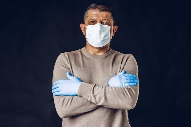 Oude man met beschermend masker en handschoenen op donkere muur. detailopname.