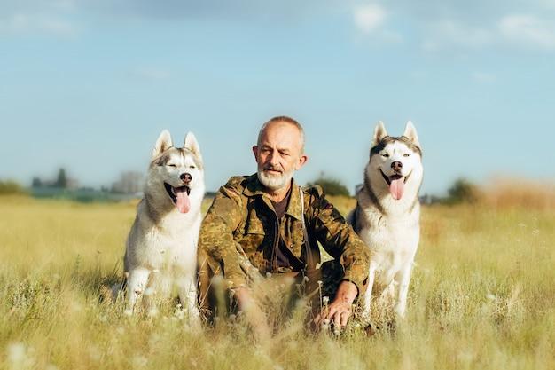 Oude man met een baard zittend op een hooiberg met hun honden, genieten van zomer zonsondergang. siberische husky op het platteland.