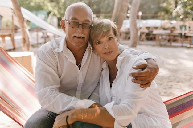 Oude man met grijze snor en bril in shirt op zoek naar camera en knuffelen blonde kortharige vrouw in witte kleren op strand.