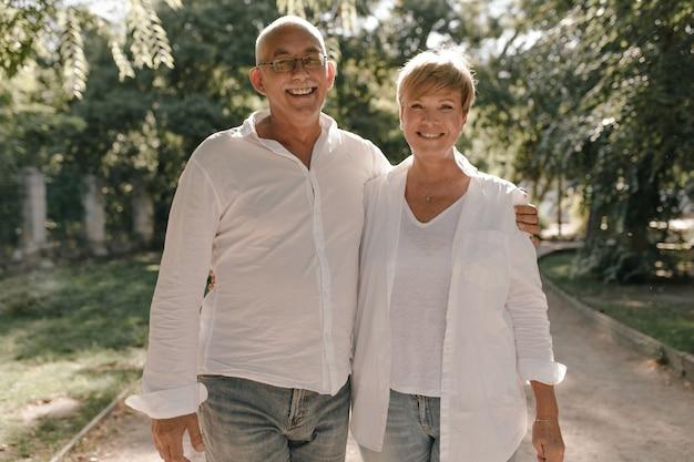 Oude man met grijze snor en bril in stijlvol wit overhemd en spijkerbroek knuffelen haar lachende vrouw met blonde haren in lichte blouse in park.