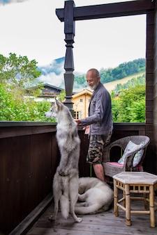 Oude man met hond siberische husky