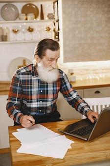 Oude man met laptop. grootvader zit in een kerstversiering. man in een celoverhemd.