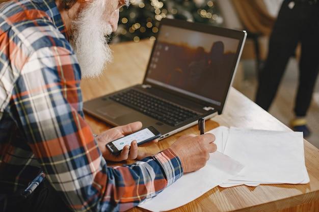 Oude man met laptop. grootvader zit in een kerstversiering. man met mobiele telefoon.