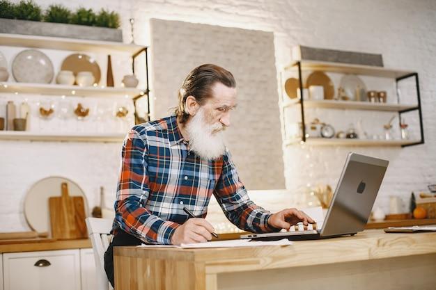 Oude man met laptop. grootvader zit in een kerstversiering.