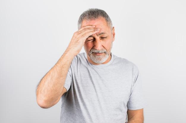 Oude man met pijn die zijn hoofd vasthoudt