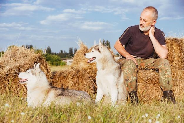 Oude man met siberische husky op het platteland.