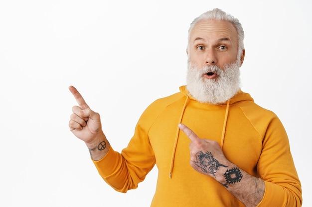 Oude man met tatoeages en lange baard die een vraag stelt over logoproduct, witte muur