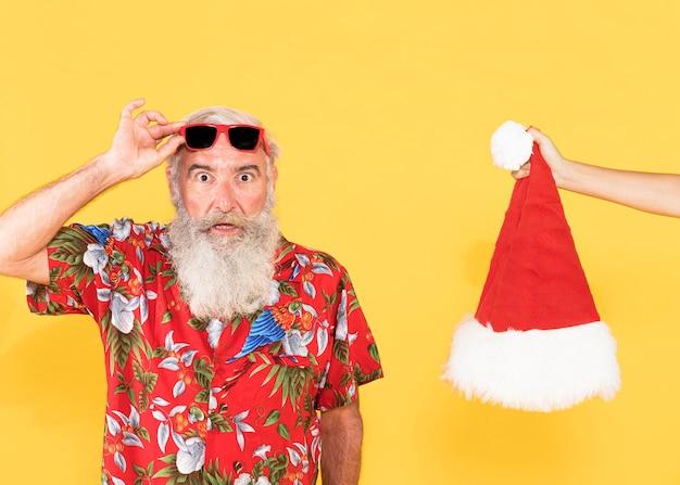 Oude man met tropisch shirt en kerstmuts