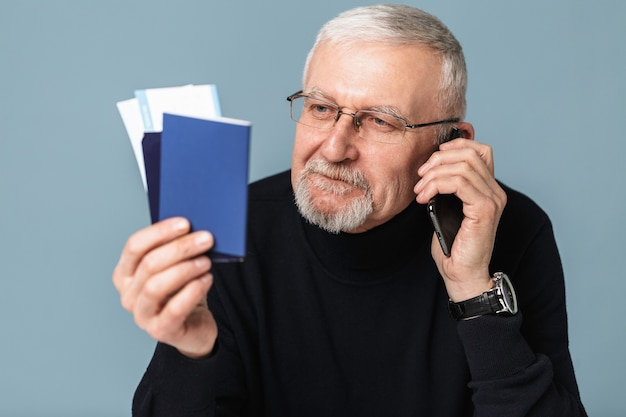Oude man met vliegtuigtickets en paspoort portret