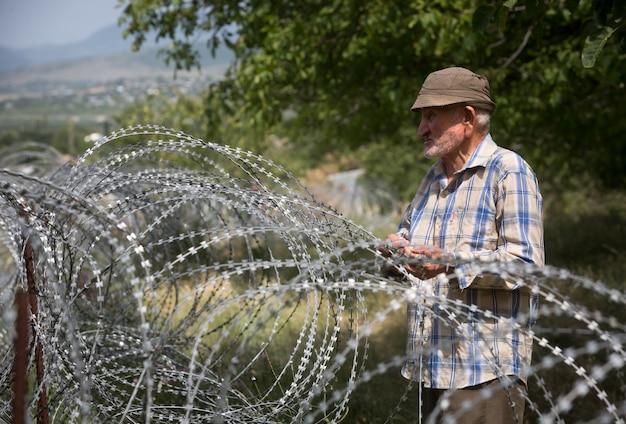 Oude man op lokale tribune bij prikkeldraad op de scheidingslijn met de bezette regio tskhinvali de feitelijke grens van georgië met zijn afgescheiden regio zuid-ossetië