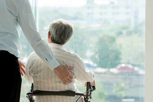Oude man op rolstoel en arts in het ziekenhuis gezondheidszorg en medische concept voor comercial
