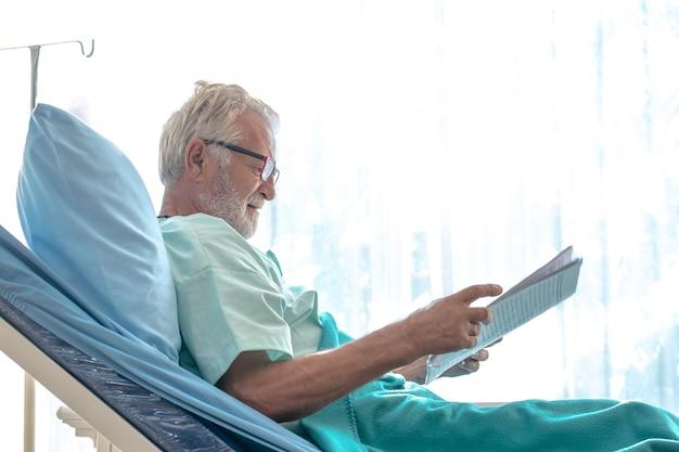 Oude man patiënt krant lezen in bed in het ziekenhuis kamer met ramen