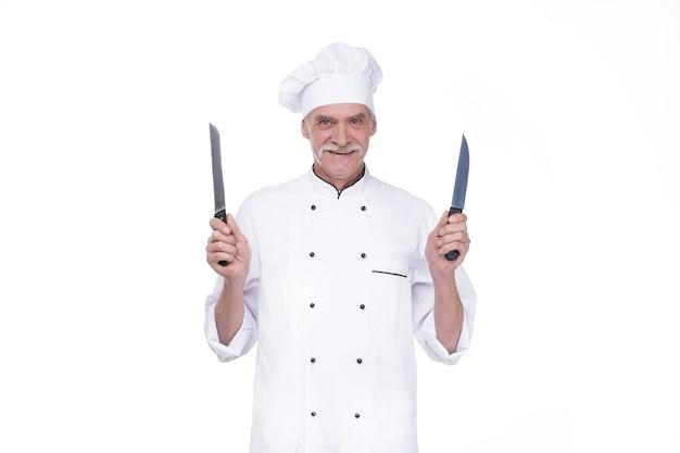 Oude man, professionele chef-kok in uniform die twee metalen mes vasthoudt terwijl hij op de witte muur blijft
