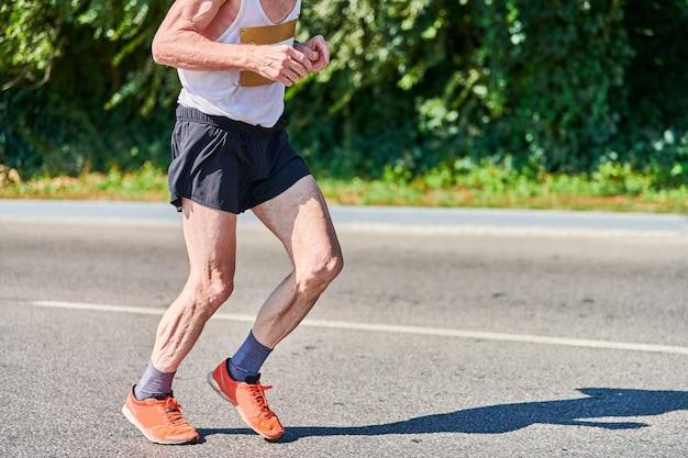 Oude man rennen. oude man joggen in sportkleding op weg van de stad