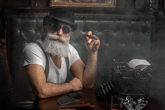 Oude man roken van een sigaar binnenshuis. maffia concept. stijlvolle man in zijn kast. bebaarde man.