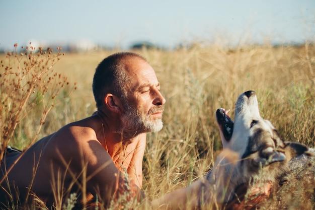 Oude man speelt met zijn hond siberische husky