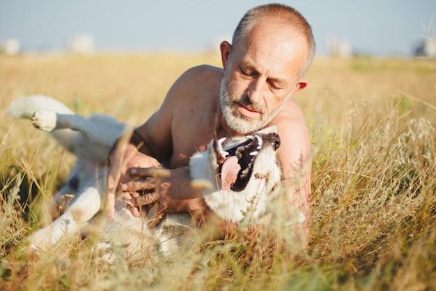 Oude man spelen met zijn hond siberische husky