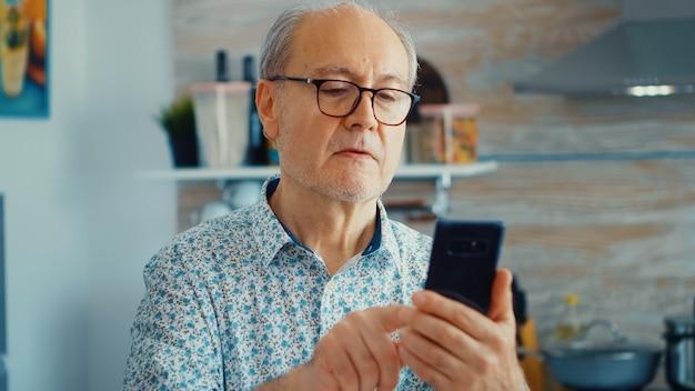 Oude man surfen op sociale media met smartphone tijdens het ontbijt in de keuken. authentiek portret van gepensioneerde senior die geniet van moderne online internettechnologie