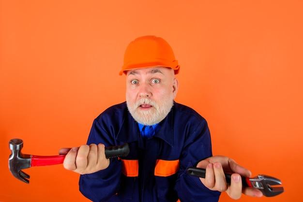 Oude man uit de bouwindustrie in een bouwhelm, een bouwer met reparatietools die aan het werk zijn