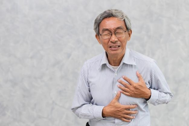 Oude man verf van hartaanval hand dekking borst met kopie ruimte