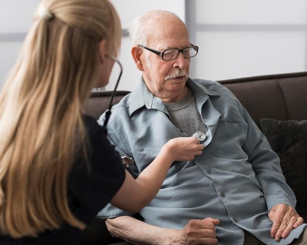 Oude man verzorgd door verpleegster