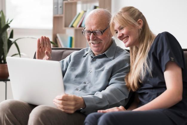 Oude man videogesprek familie uit verpleeghuis