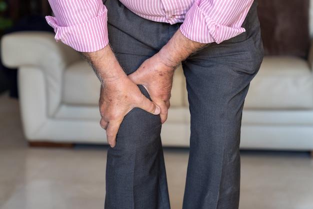 Oude man voelt pijn op zijn knie en raakt het aan
